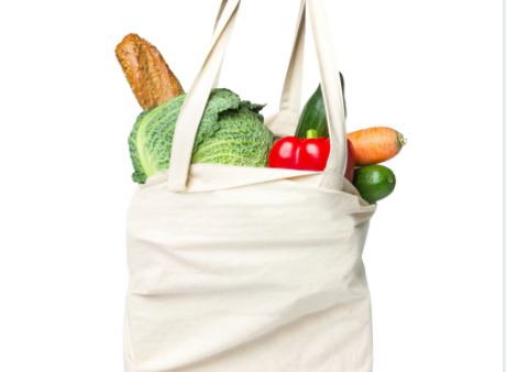 White cloth grocery bag filled with items including baguette, lettuce, red pepper and carrot.