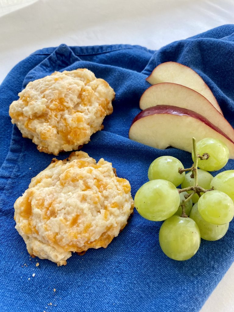 2 cheese biscuits with apple slices and grapes on a blue cloth napkin