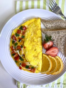 Cheese and veggie omelette on a white plate served with orange slices, strawberries and toast