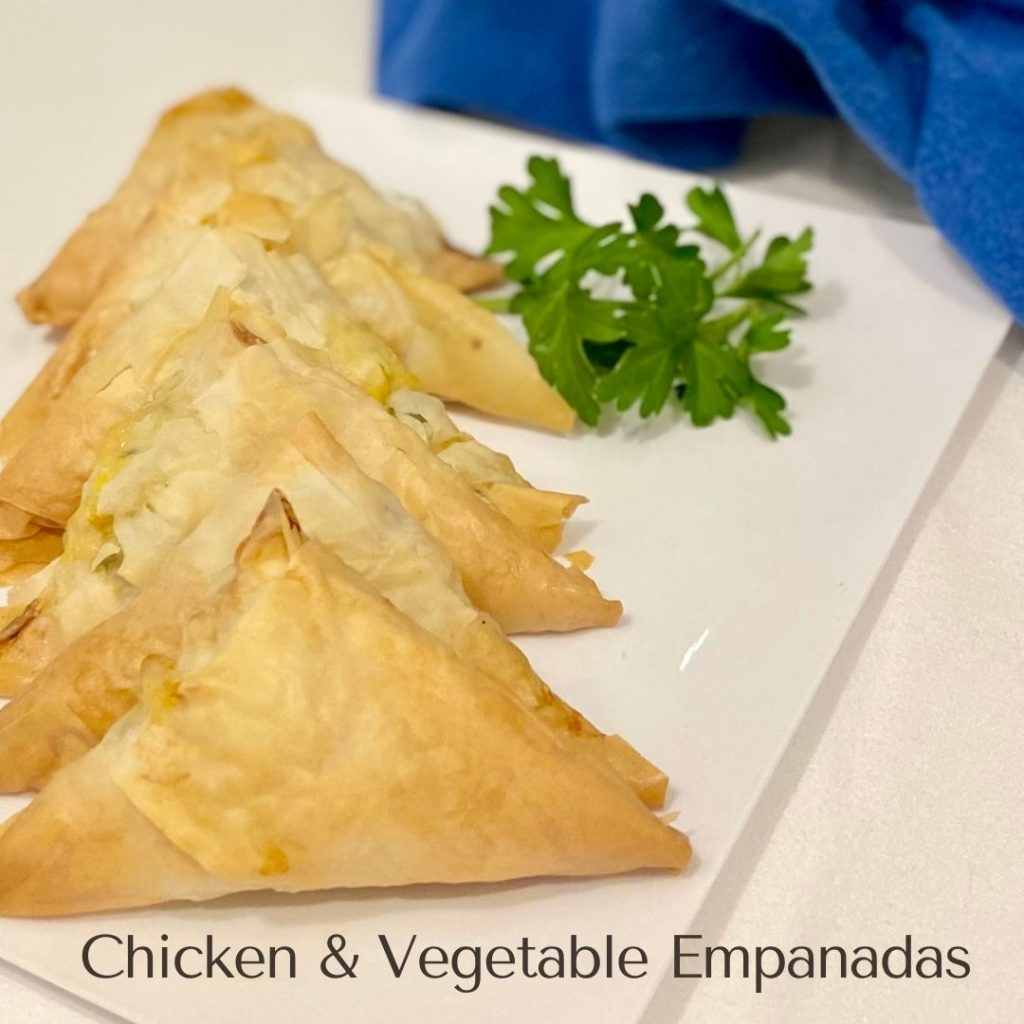 Triangular shaped empanadas stacked on a white plate with a garnish of green parsley on the side.