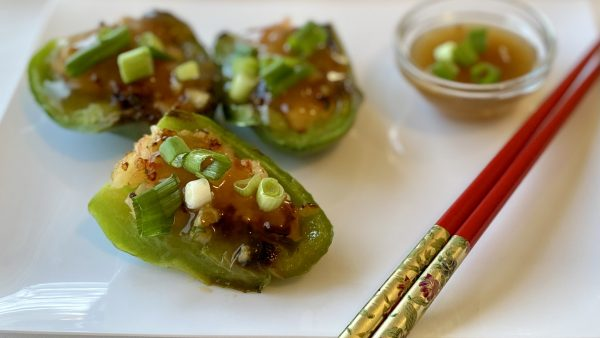Dim sum stuffed green peppers on a white platter with red chopsticks and a small bowl of sauce