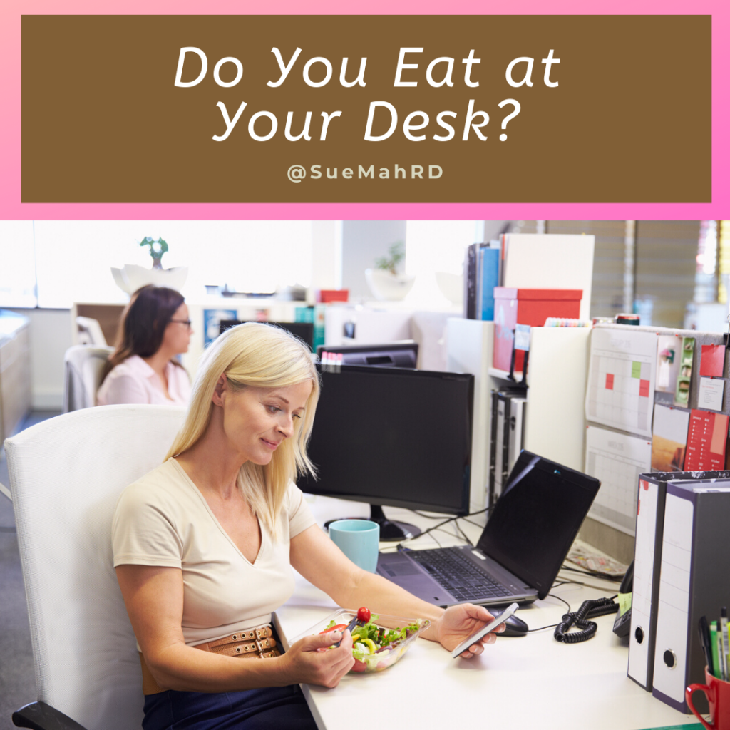 Adult woman eating lunch at her desk and reading her smart phone