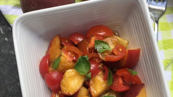 white bowl with salad made from diced peaches and diced tomatoes, garnished with basil leaves