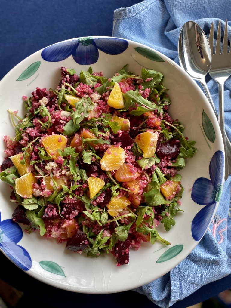 Platter of quinoa salad mixed with red beets, oranges and arugula