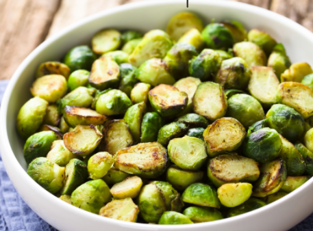 Big white bowl filled with roasted Brussels sprouts.