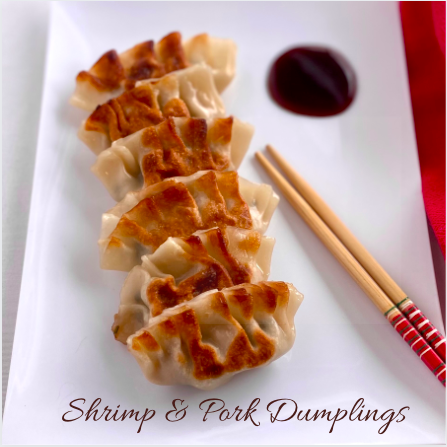 Golden browned dumplings on a plate with red wooden chopsticks beside them