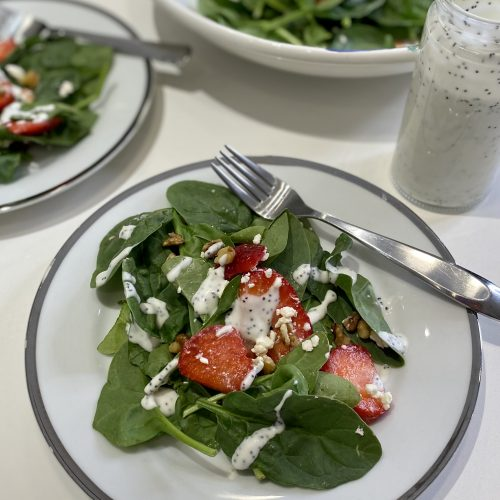 A plate of spinach salad drizzled with poppyseed dressing.