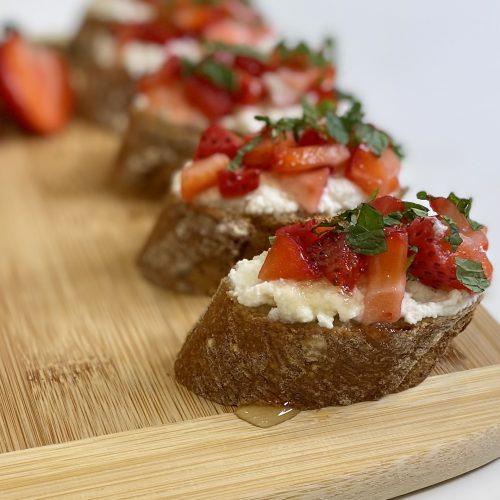 Strawberry bruschetta appetizers on a wooden cutting board