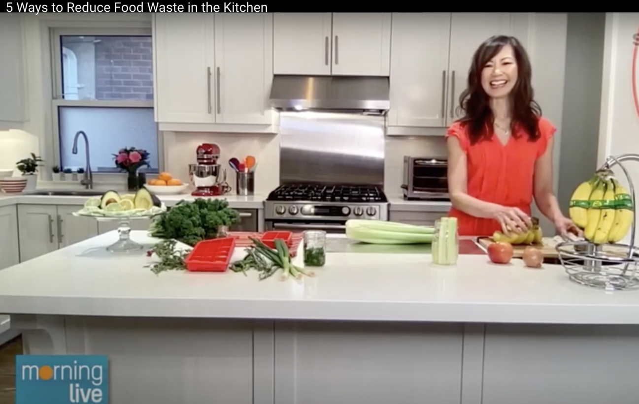 Sue wearing an orange dress and standing behind her kitchen counter which if filled with fruit and veggie props.