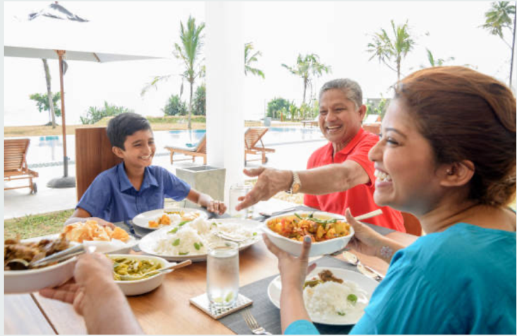 A South Asian family smiling and enjoying their cultural meal together