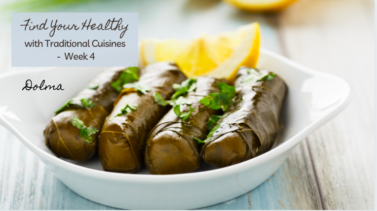 Middle Easter Dolma - grape leaves stuffed with rice and meat - arranged in a white bowl with sliced lemons in the background