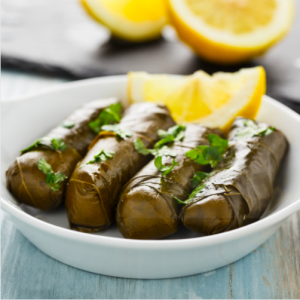 Dolma arranged on a white plate with cut lemons in the backgound