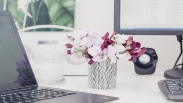 Home office desk with computer and flowers in a vase