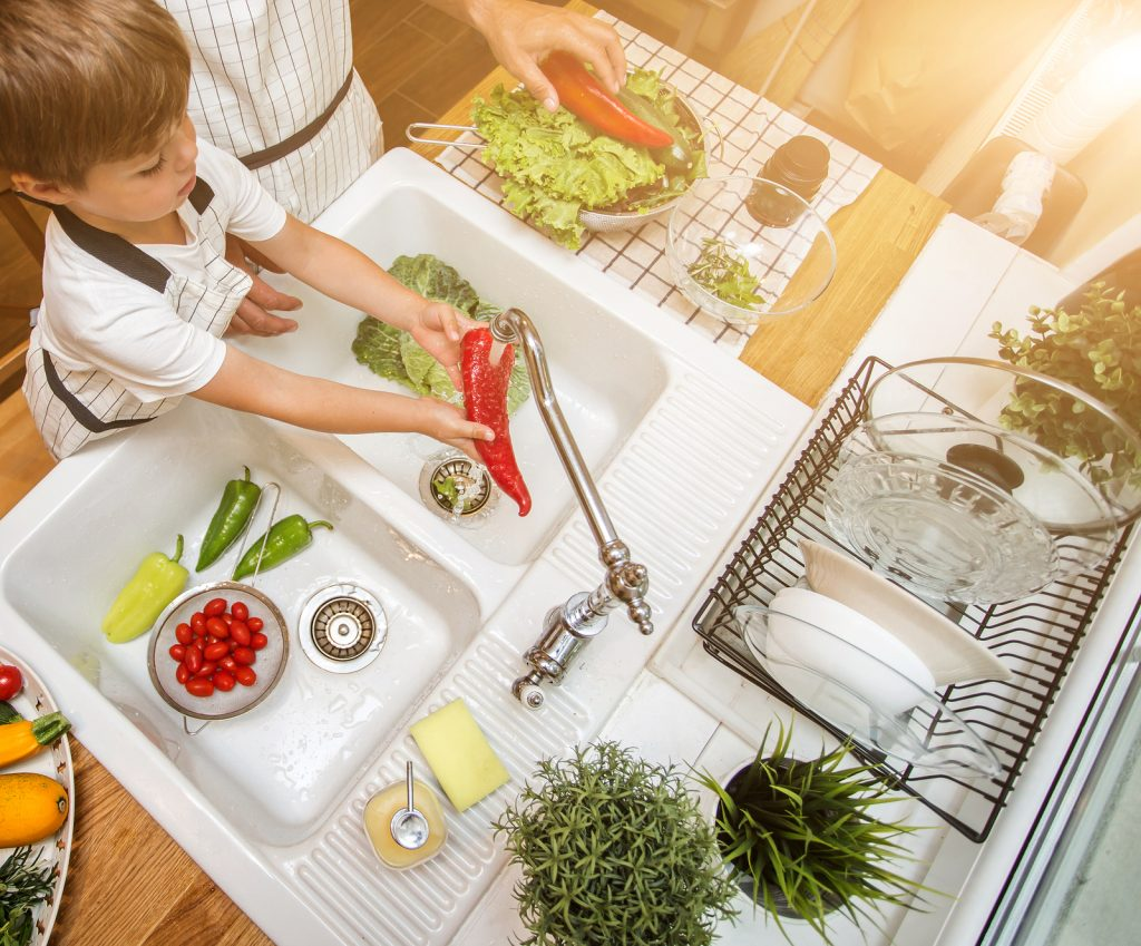 Young child washing veggies in the sink.